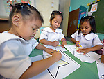 """In the capital of the Philippines, girls who live in the Manila North Cemetery enjoy drawing in class at the Santa Mesa Heights United Methodist Church. Hundreds of poor families live in the cemetery, inside and between the tombs and mausoleums of the city's wealthy. They are often discriminated against, and many of their children don't go to school because they're too hungry to study and they're often called """"vampires"""" by their classmates. With support from United Methodist Women, KKFI provides classroom education and meals to kids from the cemetery at this church."""