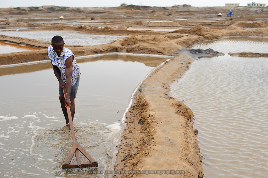 "A man raking the bottom of an ""atsiakpo"" pan to ensure that salt crystals form evenly."