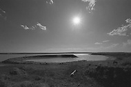 Amarillo TX,  June 1977 - An earthwork by the artist Robert Smithson, consisting of a 140 foot diameter partial circle of rock, which rises out of the level ground to a height of around 15 feet. An artificial lake was created to surround it. The lake has long since been dry and the sculpture is now eroding. Smithson was killed in a plane crash while surveying the site for this work, along with a photographer and the pilot. The crash site is a few hundred yards from the Ramp. The completion of the piece was performed by his widow, Nancy Holt, Richard Serra, and others, shortly after his death in 1973. It was commissioned by Stanley Marsh, a local ranch owner and bon-vivant who also commissioned the famous Cadillac Ranch and several other sculptures on the over 200 square miles of land he owns with his wife around Amarillo.