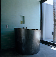 An oval zinc plunge tub stands against a wall clad in glass tiles in this modern bathroom