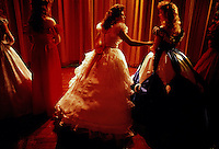 Teenage friends in lace and ruffles anxiously wait backstage for the results of the beauty pageant honoring Mr and Miss St. George.
