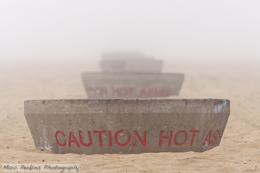 "A row of fire pits on the sandy beach appear as though they're a nesting set of matryoshka dolls (Russian nesting dolls).  Seen at Huntington State Beach in Huntington Beach, CA on a foggy New Year's eve.  They read ""Caution hot ashes"""
