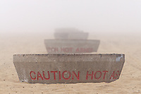 """A row of fire pits on the sandy beach appear as though they're a nesting set of matryoshka dolls (Russian nesting dolls).  Seen at Huntington State Beach in Huntington Beach, CA on a foggy New Year's eve.  They read """"Caution hot ashes"""""""