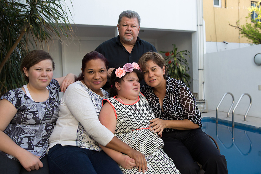 """Ana Ximena Navarro (C) and her family are pictured at their home in Guadalajara, Mexico on February 22, 2017. Ximena was diagnosed as an infant with Hurler syndrome. Hurler syndrome is the most severe form of mucopolysaccharidosis type 1 (MPS1), a rare lysosomal storage disease, characterized by skeletal abnormalities, cognitive impairment, heart disease, respiratory problems, enlarged liver and spleen, characteristic facies and reduced life expectancy. Ximena was being given enzyme replacement therapy (ERT) when she was 19 months old, and she was suddenly able to eat and sleep. She is now 12, and has normal hormonal development for her age, although some mental delay, according to her father. """"Without the treatment, she would have died from all the complications — untreated, children have a very bad quality of life and typically die before they are seven"""", her father says. Photo credit: Bénédicte Desrus"""