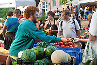 Farmers and shoppers with local, organic produce at a farmers market