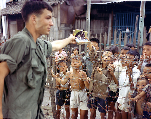 """Saigon, Vietnam - August 1, 1968 -- Private First Class (PFC) Mark W. Howard of Detroit, Michigan, a rifleman with the United States Army Company """"A"""", Third Batallion, 7th Infantry, 199th Light Infantry Brigade, buys a magazine from a Vietnamese child in Saigon, Vietnam on August 1, 1968..Credit: Burt W. Peterson - U.S. Army via CNP"""