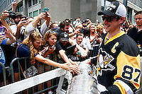 Sidney Crosby #87 of the Pittsburgh Penguins carries the Stanley Cup along the crowd of fans during the victory parade in downtown Pittsburgh, Pennsylvania on June 15, 2016. (Photo by Jared Wickerham / DKPS)