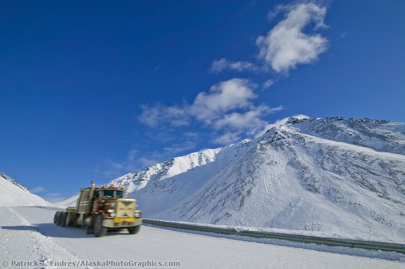 Semi tractor trailer hauls a load through Atigun pass on the James Dalton highway in winter.