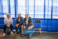 Jane Brewer, Katie Giltner, and Norton Giltner, from left, all of Batavia, Iowa, sit in the hallway after hearing Vice President Joe Biden speak at a campaign rally while on a two-day swing through Iowa on Tuesday, September 18, 2012 in Ottumwa, IA.