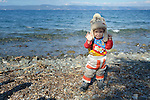 A refugee girl stands on a beach near Molyvos, on the Greek island of Lesbos, on October 29, 2015, after she and her family crossed the Aegean Sea from Turkey in a small overcrowded boat provided by Turkish traffickers to whom the refugees paid huge sums. They were received in Greece by local and international volunteers, then proceeded on their way toward western Europe.
