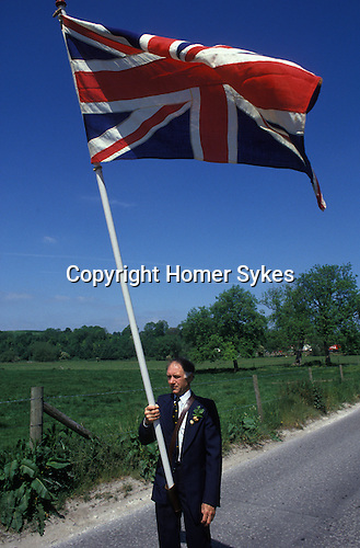 Union flag is carried at the head of the [Grovely Forest Right] procession. [Wishford Magna], Wiltshire, England &quot;Oak Apple Day