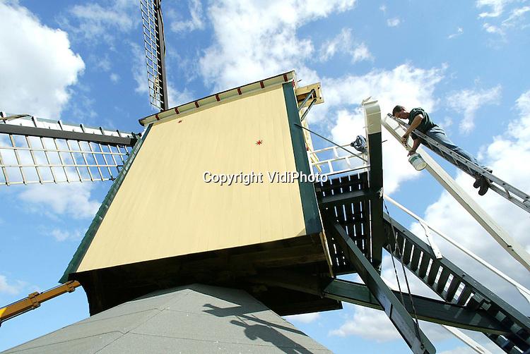 """Foto: VidiPhoto..VALBURG - Een van de oudste standerd windmolens van Nederland, """"OpNieuw Leven"""" in Valburg, wordt op dit moment door molenbouwer Coppes uit Bergharen onder handen genomen. Behalve schilderwerkzaamheden aan de buitenkant, moet het houtwerk aan de binnenzijde goed nagelopen worden. Door de droogte deze zomer kunnen er door loszittende bovenwielen gevaarlijke sitauties ontstaan. Diverse molens hebben daar nu last van."""