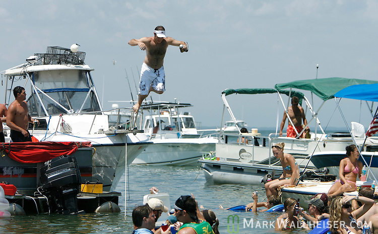 Jerome Dwaltey (C) jumps off the bow of a boat after getting a fresh beer during the 2006 White Trash Bash May 28, 2006. The White Trash Bash is a annual boat party at Dog Island, a remote island off the Florida panhandle 75 miles south of Tallahassee.  This year's party drew thousands arriving in over 350 boats.    (Mark Wallheiser/TallahasseeStock.com)