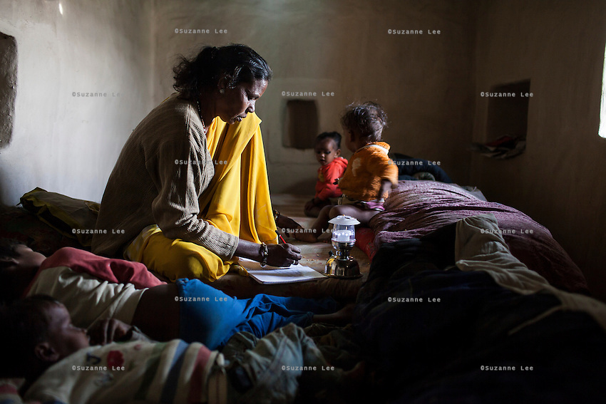 Shanti Adivasi, 52, works without electricity on her interview notes while her granchildren play around her on a row of beds she shares with her family of 14 in Manikpur, Chitrakoot, Uttar Pradesh, India on 6th December 2012. Shanti used to be a wood gatherer, working with her parents since she was 3, and later carrying up to 100 kg of wood walking 12km from the dry jungle hills to her home to repack the wood which sold for 3 rupees per kg. After learning to read and write in an 8 month welfare course, at age 32, she became a reporter, joining Khabar Lahariya newspaper since its establishment in 2002, and making about 9000 rupees per month, supporting her family of 14 as the sole breadwinner. Photo by Suzanne Lee for Marie Claire France.