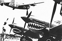 Landing wheels recede as this U.S. Army Air Forces Liberator bomber crosses the shark-nosed bows of U.S. P-40 fighter planes at an advanced U.S. base in China.  An American soldier waves good luck to the crew, off to bomb Japan.  Ca. 1943. Acme. (OWI)<br /> Exact Date Shot Unknown<br /> NARA FILE #:  208-N-15394<br /> WAR &amp; CONFLICT BOOK #:  1150