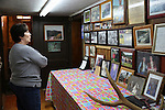Marlene Feltner reflects on her family history in her fathers farm house in Wendover, Ky., on Friday, October, 11, 2013. Her fathers farm house is now used for family events and this wall houses family photos and memorabilia. Photo by Rachel Walker