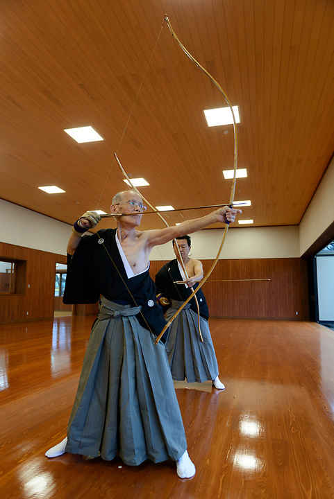 Archery students, Kyudo Practice Hall, Miyakonojo, Miyazaki Prefecture, Japan, December 22, 2016. A handful of bowyers from the Kyushu city of Miyakonojo make over 90% of all the bows used in traditional Japanese archery. The bows are made from laminated bamboo and haze wood in process that consists of over 200 individual tasks. At over two meters from tip to tip the bows the longest used in the world.