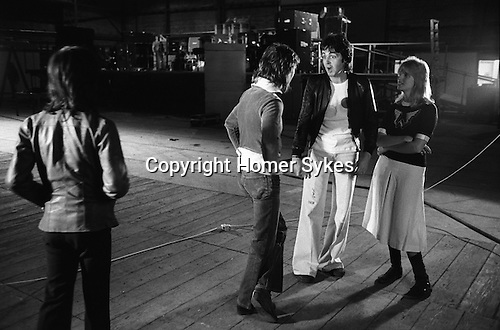 Paul and Linda McCartney Wings Tour 1975. Paul and Linda talking to Denny Laine. They have just had an official Wings group photograph taken. Elstree rehearsal studio London England..