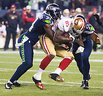 San Francisco 49ers tight end Vernon Davis (85) is hit by Seattle Seahawks strong safety, Kam Chancellor, (31) and linebacker Bobby Wagner (54), during the NFL  Championship Game at CenturyLink Field in Seattle, Washington on January 19, 2014.  The Seahawks beat the  49ers 23-17 to represent the NFC in the Super Bowl. ©2014. Jim Bryant Photo. ALL RIGHTS RESERVED.