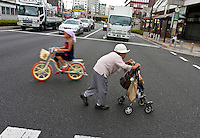 An older Japanese woman using a walking aid crosses a street in Sugamo, Tokyo, Japan. Friday, August 14th 2009. Sugamo is affectionately known as the old lady Harajuku, in reference to the Mecca for youth fashions in the South of Tokyo, and is a popular place for Tokyo's increasingly aged population.