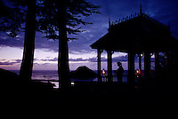 Lanterns illuminate a lone girl in a gazebo overlooking the Pacific coast south of Mendocino. Winter storm clouds clear at dusk.