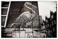 Big bird by artist Roa on a building wall, Shoreditch, East London
