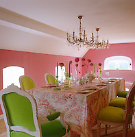 In the dining room the pink of the walls is echoed in the toile de Jouy tablecloth and vividly contrasts with the grass green fabrics covering the 19th century chairs