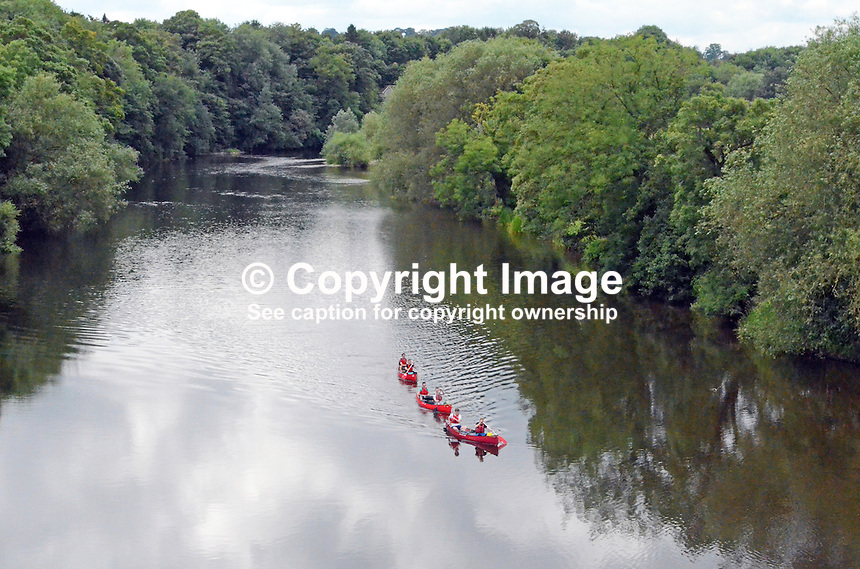 Canoeists on tree-lined River Wye at Hay-on-Wye, Herefordshire, UK, July 2014, 201407053260. <br />