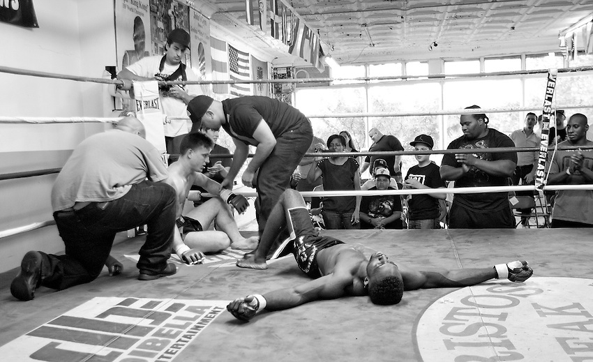 BRONX, NY - (Aug., 24, 2013) -The referee, left, and promoter Peter Storm check the condition of fighter James Funaro, who sits up after he was beaten by Jerome Mickle (right) who then collapsed after he won the main event of an unsanctioned MMA card hosted by Underground Combat League at John's Boxing Gym in the South Bronx.