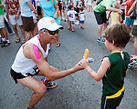 Emil Magallanes passes on an ice cream bar to his son, Kai, following the finish of the Meadow Gold Children's Half Miler during the Main Street Mile sponsored by Saint Alphonsus in downtown Boise, Idaho on June 22, 2012. Kai, age 5, completed the half mile in 4:28.2.