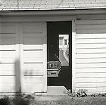 Lewisburg alleyway with garage door opened and pathway to old house. 1976