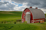 Washington, Eastern, Steptoe, Palouse Region.  A red barn, silo and vintage truck under partly cloudy skies in spring.