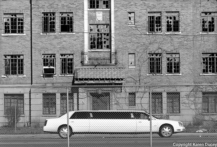 "A limousine in town for the Miss USA Beauty Pageant passes by one of Gary's many dilapidated buildings.  In an effort to improve the city 253 buildings were demolished last year. ""The city may not have been ready"" explains Richard Grey, managing editor of the local paper the Post-Tribune, ""but if you wait until you're ready you're never gonna have these things.""..."