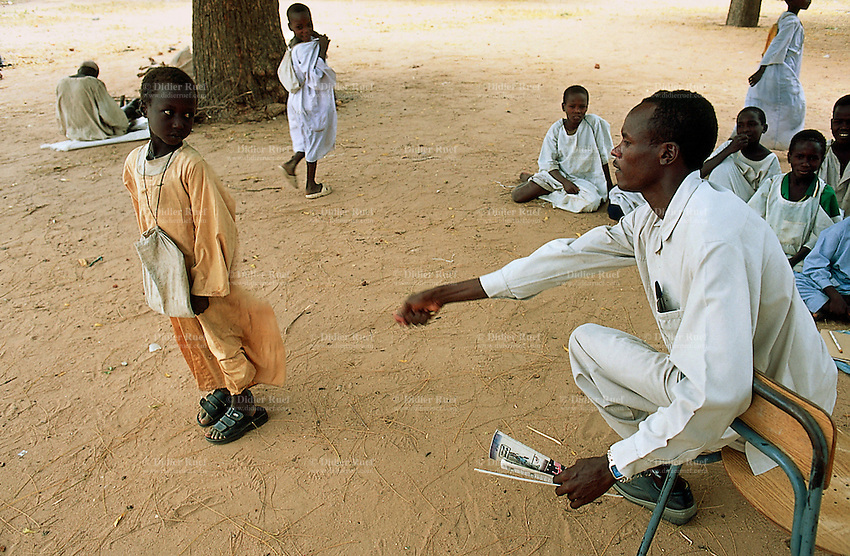Sudan. West Darfur. Habilah. Public school. A teacher punishes a pupil by beating him with a stick on his buttocks. The other children sit on the ground to listen to lesson. © 2004 Didier Ruef