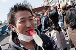 A Japanese sucks on a penis shaped candy during the Kanamara matsuri or festival of the iron phallus in Kawasaki Daishi near Tokyo, Japan. Sunday April 1st 2012