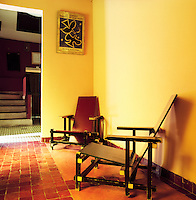 A pair of Rietveld chairs sits in the corner of a terracotta tiled room