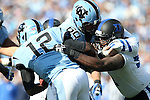 30 November 2013: Duke's Jamal Bruce (right) fights through a block by UNC's Russell Bodine (60) to grab Marquise Williams (12). The University of North Carolina Tar Heels played the Duke University Blue Devils at Keenan Memorial Stadium in Chapel Hill, NC in a 2013 NCAA Division I Football game. Duke won the game 27-25.