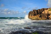 At sunrise, a wave breaks against the pinnacles along Maha'ulepu Heritage Trail on Kaua'i's southern shore.