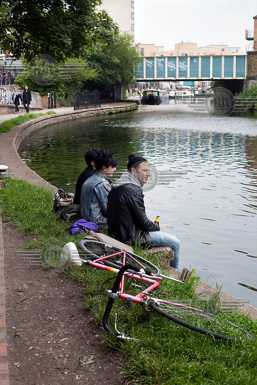 Three people sit and drink on the banks of the Regent's Canal, London Fields, Hackney, East London.