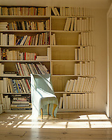 A symbolic library of all-white bound books is placed next to the colouful jackets of a collection of paperbacks and magazines