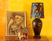 Detail of a charcoal drawing, a lampshade by Yves Saint Laurent and an intricate box on a console table in the living room