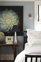 A guest bedroom is decorated in a fresh pale green and white with an over-sized photograph of a dahlia on the wall