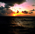 The sun sinking below the horizon of the Pacific Ocean.