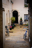 Three bicycles parked in a courtyard off a busy street in London, England.
