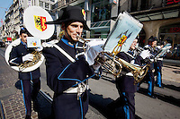 Switzerland. Geneva. Policemen from police band play music and walk on the day in which young policemen and policewomen from the police academy will be sworn in as police officers. They wear uniforms, white gloves, tricorns on the heads. They play the trumpets and the sousaphone. The trumpet is the musical instrument with the highest register in the brass family. The sousaphone is a type of tuba that is widely employed in marching bands. Designed so that it fits around the body of the musician and is supported by the left shoulder, the sousaphone may be readily played while being carried. The tricorne or tricorn is a style of hat that was popular during the 18th century, falling out of style by 1800. The tricorne was worn as part of military uniforms. The flag of Geneva is divided vertically into two equal parts, yellow (hoist) and red (fly). In the hoist, a black double-eagle with a red crown, beak, tongue, legs and claws, cut in half by the palar line. In the fly, a yellow upright key with its ward toward the fly. The eagle symbolises loftiness, justice and protection. The key symbolises ecclesiastical rule, treasuries, and responsibility. The arms of Geneva are actually two shields impaled: half the eagle of the Holy Roman Empire, and one of the two keys of St. Peter (the &quot;keys of heaven&quot;. 29.08.12 &copy; 2012 Didier Ruef...