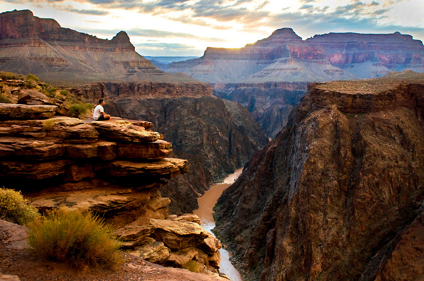 A hiker enjoys a surreal sunset at Plateau Point within Grand Canyon.