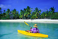 Kayaker paddles toward motu in the blue lagoon off Aitutaki, Cook Islands