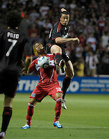 AC Milan defender Massimo Oddo leaps over the shoulder of Chicago Fire midfielder Mike Banner (18) to get the ball.  AC Milan defeated the Chicago Fire 1-0 at Toyota Park in Bridgeview, IL on May 30, 2010.