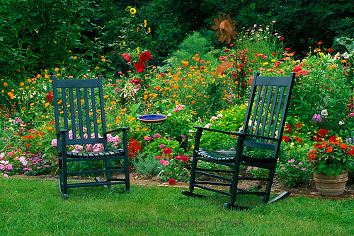 Two painted green rockers in colorful garden with copper statue, ceramic bird bath, and mulit-colored blooms in summer