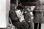 Blind man playing accordian along street during winter downtown Seattle with little boy putting coins in tin can Washington State USA